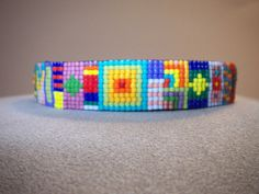 Mardi Gras is a multi-colored beaded cuff using opaque Miyuki delica, high-intensity fired, glass beads. It measures 5/8 of an inch wide. The