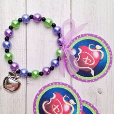 Descendants apple charm bracelet. It is a 6.25 inch bracelet on stretchy cord with round green, purple and blue pearl beads and a silvertone