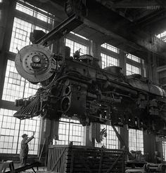 """March 1943. Albuquerque, New Mexico. """"Lifting an engine to be carried to another part of the Atchison, Topeka & Santa Fe shops for wheeling...."""