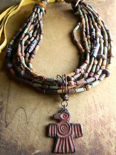 Tribal necklace design with lots and lots of wampum beads (Czech aged tube beads) in a southwestern style with leather and artisan ceramic caps. Eight strands of aged tube beads mixed with bone and more Czech aged finish beads provide a richly colored backdrop for the native American bird pendant and its ruddy red patina. The artisan pendant was made by my friend, Vincent Cav, of Inviciti Jewelry. To this luscious combination of textures and colors, I have added dark yellow deerskin lacing…