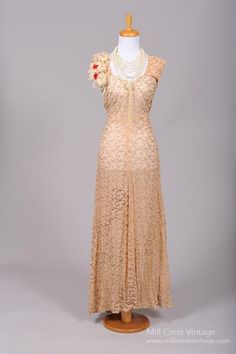 Designed in the 40's, this elaborate vintage wedding gown is done in a soft apricot toned sheer silk chiffon adorned with a swirl pattern done in silver meta...