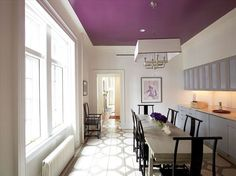 dining room: purple plum ceiling, grey cabinets, table, black chairs, stencil floor, white wall.