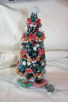 """Decorated with snowflakes, gingerbread men glass and plastic balls, candy canes tied with red bows and Santa face cookies. Nicely decorated & Flocked Christmas brush tree is signed """"MINIKINS JOANN TRAINOR"""".   eBay!"""