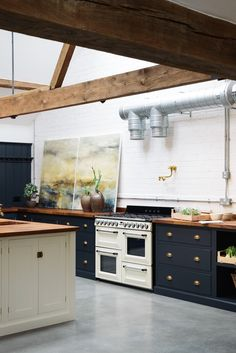 one design for the kitchen, bottom cabinets dark blue, gray, with painted countertops, and white above cabinets, with a stenciled floor in the kitchen that goes into the laundry room