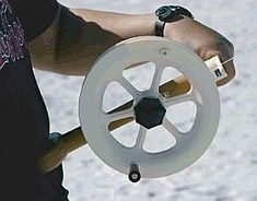 A white kite reel with winding handle and braking.