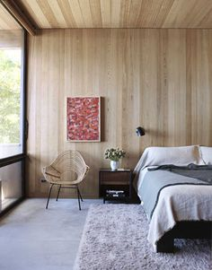 Relaxed and uncontrived, the master bedroom has old-growth cypress paneling glowing on its ceiling and walls. The linen fringe bedcover by G.T. Design is from Ruby Beets Old & New; the bamboo chair is a vintage find from Home. The painting is by a neighbor, Margaret Garrett.
