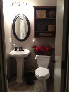 Small bathroom remodel. Gerber Allerton pedestal sink, Gerber avalanche toilet, custom shelf, Benjamin Moore sandlot gray paint, mirror and baskets from Hobby Lobby, kohler shower stall (not shown).