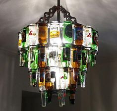 The beer bottle chandelier is the ultimate lighting source for a home bar or enclosed patio. Made from real beer bottles, the beer bottle chandelier is a beautiful source of light that displays many colors and makes a great house warming gift. Beer Bottle Chandelier, Beer Bottle Lights, Recycled Bottle Crafts, Recycled Glass, Recycled Art, Beer Bottle Crafts, Craft Beer, Beer Crafts, Empty Bottles