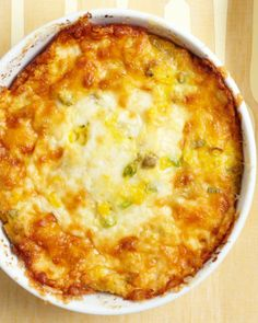 24 oz frozen corn (4 c.), thaw and puree,      1 tsp coarse salt     3 scallions, thinly sliced     1 can (14 o) Hatch green chiles, diced     3 Tbs all-purpose flour     2 c. grated Monterey Jack (6 oz), reserve some for top     5 lg eggs,      2/3 c. heavy cream     1/2 stick unsalted butter bake 350 degrees