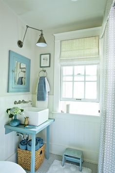Clever cottage bathroom. The sink base is designed to take up very little room but the towel storage is terrific.