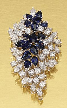 SAPPHIRE AND DIAMOND BROOCH, 1960S.  Designed as a stylised leaf set with a central cluster of pear-shaped sapphires within surrounds of marquise-shaped and brilliant-cut diamonds.