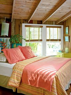 Key West, Florida bedroom...rustic wood paneling & bright bed linens play off the lush tropical vegitation outside.