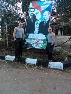 Russian soldiers posing in Syria next to a banner showing Russian President Vladimir Putin and his Syrian counterpart Bashar al-Assad, while Russia continues to deny its presence there.