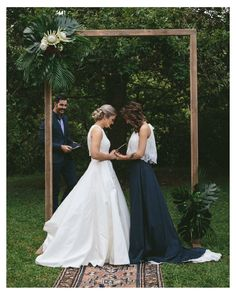 Lesbian Wedding - the contrast between the white and the black dress, and that arbor <3