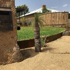 Rock letter box, corten steel garden edge, latte pole screen & native plants.