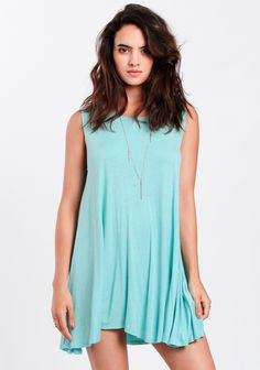 Bright aqua-blue tank dress constructed with a flowy trapeze silhouette and a rounded neckline. Accessorize it with a hat and layers of necklaces or add a belt for a more defined waistline.