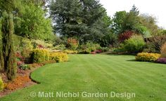 Mixed borders and mature trees frame the landscaped lawn.