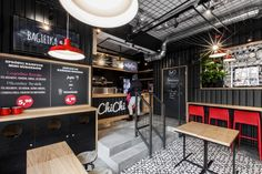 Suspended ceiling made of black steel mesh reveals silver technical ducts expand the raw and industrial atmosphere of the place.