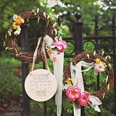 Flower-trimmed wreaths and a sign welcomed the couple's guests to the ceremony. Photo: Kyle Hale.