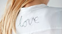 Met liefde gemaakt, zeg het met teksten. Geef je kleding of accessoire een nieuwe look met een mooi woord of een vrolijke quote!Benodigdheden:- Blouse- Papier- Potlood- Naaimachine- Zwart garenZo maak je het:Schrijf de tekst op het stuk papier en leg het onder de stof, trek de tekst over met potlood direct op de blouse. Naai met een siersteek de tekst op het kledingstuk.TipJe kunt de tekst er ook op borduren met een kruissteek in fluorkleur.Credits: Maaike van Haaster