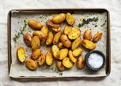 Υλικά: 1 κιλό νεαρές πατάτες 2 κ.σ. ελαιόλαδο 2 σκελίδες σκόρδο τριμμένες 1 κλωνάρι φρέσκο δενδρολίβανο, (κρατάμε τα φυλλαράκια και τα ψιλοκόβουμε) 3 κλωνάρια φρέσκο θυμάρι, (κρατάμε τα φυλλαράκια και τα ψιλοκόβουμε) χοντρό αλάτι κατά προτίμηση φρεσκοκομμένο πιπέρι Εκτέλ