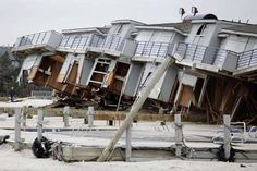 A man walks past a cabana complex on the beach pulled off its foundations by Superstorm Sandy in Sea Bright, N.J., Monday, Nov. 19, 2012. Sea Bright, the state's narrowest barrier island, was decimated by the storm, pummeled by waves from the ocean to the east and flooding from the Shrewsbury River just two blocks away on the west side of town. (AP Photo/Seth Wenig)