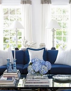 Like the glass coffe table and sofa table behind the couch with a pair of white lamps. blue and white living room