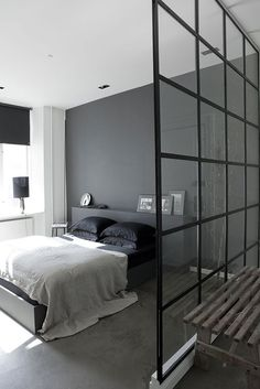 Elegant dark bedroom behind an industrial glass wall.