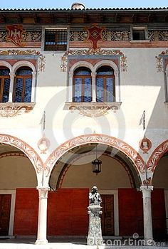 Photo made in the province of Trento in Rovereto (Italy). In the picture, made in one of the squares of the city, you see part of the facade, richly decorated with frescoes, of an ancient and important building. At the central portico a pendant lamp and a statue are at.