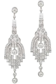 A pair of diamond pendant earrings circa 1925, each designed as a graduated series of links set with baguette and circular-cut diamonds. French marks. Diamonds weight: approximately 10 carats.