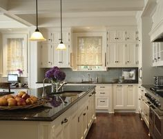Dark granite countertop, white cabinets, blue backsplash