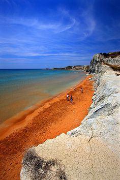 "One more of the many splendid beaches of Kefalonia, under the strange name ""Xi"". It is famous for its deep orange, almost red, sand, making a great contrast with the white rocks. It is located on the southwest part of the island"