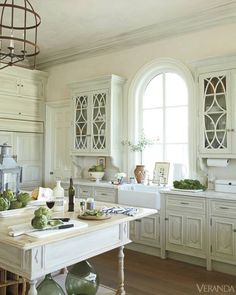 Arched Window over Farmhouse Sink with beautiful detail on the doors