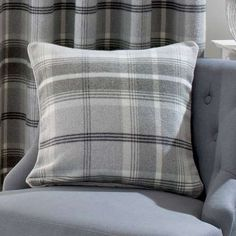 Filled with feather, this grey square cushion features a removable cover finished in a tartan style with piped edging....