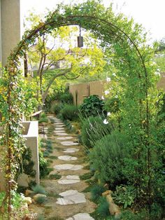 Garden designer Shirley Bovshow created a timeless appeal in this narrow passageway with vintage, rusted metal and recycled concrete stepping stones.