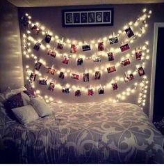 String up xmas lights. Use clothespins to hang pictures on the light strings. So cute!