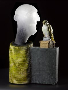 Exchange of Information IV, cast glass, cylinder supporting an opaque head of a man with open mouth, facing a brightly coloured bird perched on a buff box on top of grey slabs: England, Norfolk, Dickleburgh, David Reekie, 2007.