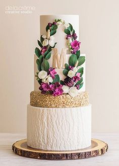 Sugar flower wreath surrounds the couple's monogram.  Love the white bark bottom tier and the gold sequins above.
