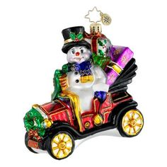 This collectible glass Christmas ornament features Frosty riding in style at the wheel of a shiny vintage Ford Model T, piled high with highly detailed presents and decorated for Christmas. Description from radko-christmas.com. I searched for this on bing.com/images