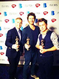 Gary Barlow, Howard Donald and Mark Owen collecting Take That's 'Contribution to British Music' Ivor Novello award.