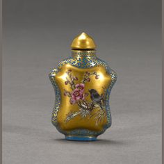 An enameled porcelain snuff bottle  Qianlong mark  Of quatrefoil form and raised on a high oval foot ring, painted with birds perched on a branch of peonies and plums, elegantly rendered in famille rose enamels reserved on a gilt ground enclosed by a border of gilt leafy foliage on a pale blue ground, four-charater Qianlong mark in red enamel at the base.  2 1/4in (5.7cm) high  Estimate: US$ 2,500 - 4,000  gbp1,600 - 2,500  €2,000 - 3,100