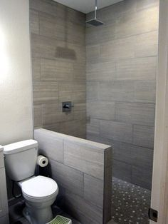 DIY basement bathroom finish. Modern gray tile floor to ceiling shower with rainfall showerhead. Half wall and a walk-in shower with mosaic gray and white glass tile on the floor. See the before and after pics!
