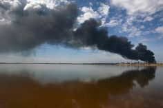 A column of smoke rises, a day after an explosion at Amuay oil refinery in Punto Fijo in the Peninsula of Paraguana