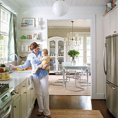 All white walls, cabinets, and countertops in the design make this space seem bigger. To keep the room from feeling too flat, the homeowner added color and texture with accessories such as curtains and a jute rug. She reinforced the vintage look of the house with a new tongue-and-groove wood-plank ceiling and a trio of oversize globe lights, which were splurge items.