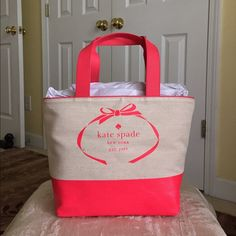 """Authentic KateSpade Heritage Spade Logo Tote Authentic Kate Spade Heritage Spade Logo Tote Bag. Style PXRU5584. Color- light tan canvas fabric with Geranium (coral orangy) leather trim, design bottom and front logo. Open top with dog clip closure, with zip pocket inside but has no fabric lining. Dimensions- 12.5"""" L (bottom) or 15.5"""" L (top) x 11.25"""" H x 6"""" W and handle drop height of 9"""". No dust bag included. kate spade Bags Totes"""