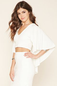 A knit crop top with a V-neckline and a cape overlay that creates short sleeves and continues to its back.