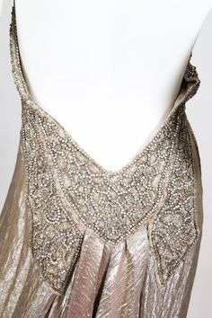 rose-gold silk lamé gown from the 1930s. The incredible fabric falls in gentle, crinkled flutes in front, and in a waterfall of rippling metallic silk from the double box pleat in back. The sweetheart neckline is edged by a crystal and bead-encrusted halter neck border. The crystals and beads wrap around to the back and down to the base of the spine and widens into a winged V-shape, from which the back pleats tumble.