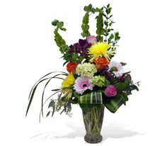 Colourful and stylish glass vase arrangement variegated aspidistra leaves, Bells of Ireland, gerbera daisies, roses, spider mums, mini green hydrangea, alstromeria, variegated aspidistra leaves, seeded eucalyptus and lily grass. By Caruso & Company