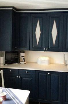 Puuvalmis JUVIn keittiö maalattiin tummansiniseksi. Osa kaapinovista koristemaalattiin.