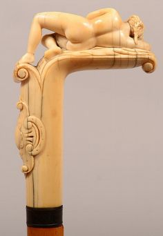 "Victorian Semi-nude Carved Ivory Cane. Gracefully carved reclining beauty cloaked in a cloth sheet above a well executed cartouche. Unmarked silver band and maple shaft. Handle measures 4"", overall length is 35""."